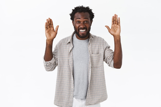 Amused and carefree african-american bearded guy with amused, enthusiastic expression