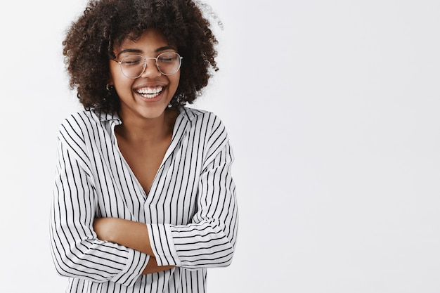 Amused and carefree attractive african american woman in striped blouse and glasses closing eyes laughing out loud and holding hands on chest closing eyes having fun