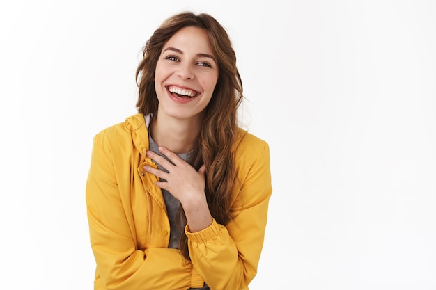 楽しそうに笑うのを楽しんでいるのんきなフレンドリーな若い優しいきれいな女性は、胸をくすくす笑うスタンドアップコメディパフォーマンス立っている白い壁を楽しませて明るい気分を楽しませてください