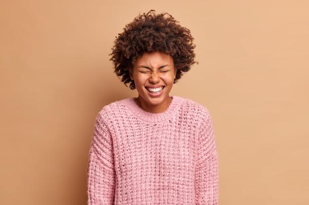 즐거운 평온한 여자가 눈을 감고 미소를 지으며 순수한 감정을 넓게 표현합니다. 재미있는 친구가 베이지 색 벽에 따뜻한 니트 스웨터 포즈를 입고 큰 소리로 웃음