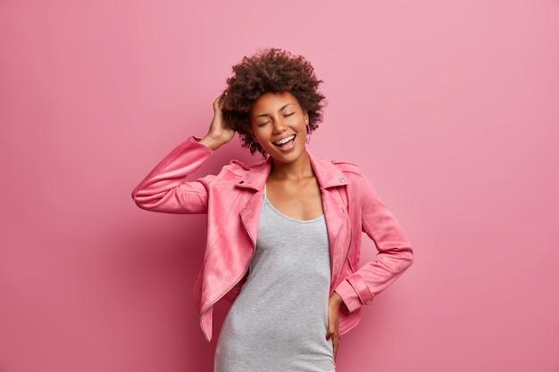닫힌 눈을 가진 평온한 젊은 아프리카 계 미국인 여성을 즐겁게하고 멋진 하루를 즐기고 세련된 옷을 입고 넓게 미소지었습니다.