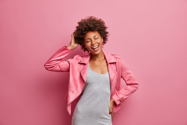 Amused carefree young afro american woman with closed eyes, enjoys awesome day off, dressed in stylish clothes, smiles broadly