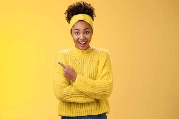 머리띠 스웨터를 입은 카리스마 넘치는 웃는 검은색 귀여운 소녀는 눈을 크게 뜨고 턱을 괴고 놀라서 왼쪽을 가리키는 노란색 배경에 서 있는 친구가 서 있는 놀랍고 흥미로운 새로운 장소에 대해 듣습니다.