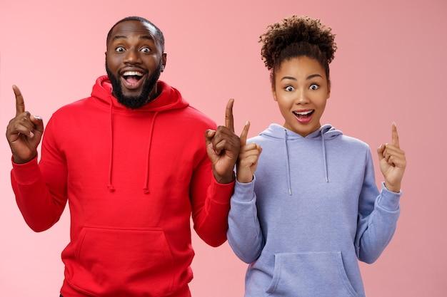 Веселые харизматичные два лучших друга афроамериканец брат сестра показывает поднятыми указательными пальцами вверх широко раскрытые глаза впечатлен весёлый чувствовать себя счастливым поехать учиться за границу вместе выиграть поездку стоя удивленный