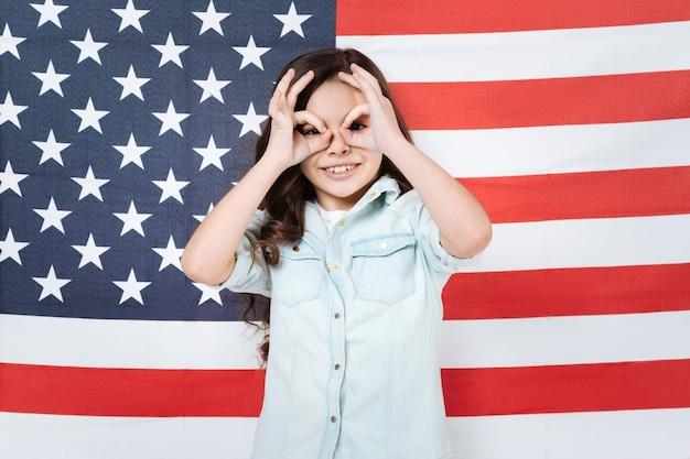 Веселая веселая довольная девушка веселится и выражает радость, стоя против американского флага