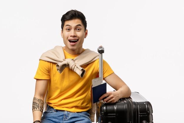 面白がって、陽気なハンサムなアジアの若い男性の学生が最終的に海外の友人を旅行し、空港の搭乗で待って、黒いスーツケースに座って、荷物を詰め、夢のような白い壁を笑顔