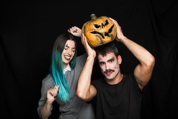 Amused company with orange pumpkin