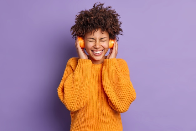 Amused dark skinned woman enjoys xmas holiday playlist in headphones closes eyes and smiles toothily wears orange jumper poses over vivid purple background. music lover indoor satisfied with sound