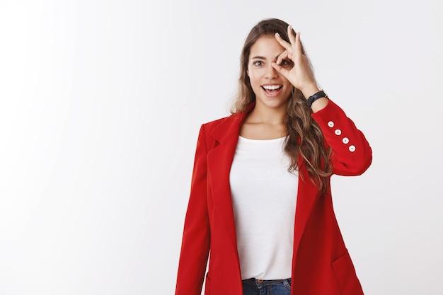 Веселая восторженная мечтательная великолепная кудрявая кавказская девушка в красной куртке, смотрящая через жест `` окей '', изумлена, взволнована, с открытым ртом, изумлена, видя возможности, белая стена