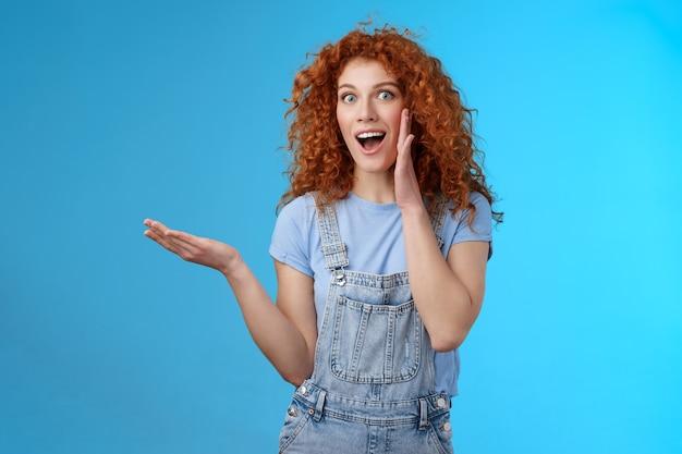 Веселая возбужденная привлекательная веселая рыжая кудрявая девушка представляет потрясающий продукт, поднятую руку, пустую синюю копию пространства делится секретным промо-предложением ладонь возле открытого рта на фоне студии.