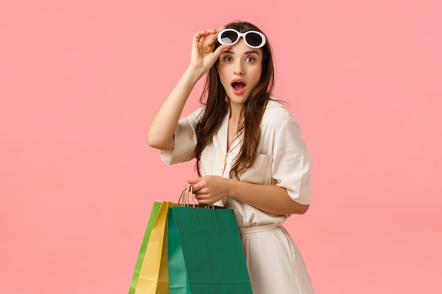 Amused feminine girl, waisting all money on new clothes, found favorite store, holding shopping bags and gazing excited, taking-off glasses seeing something fantastic, pink wall
