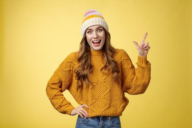 Divertito amichevole giovane ragazza in uscita divertirsi parlando amici divertito a discutere cool promo indicando l'angolo in alto a destra sorridente felicemente parlando casualmente entusiasta sguardo fotocamera, sfondo giallo