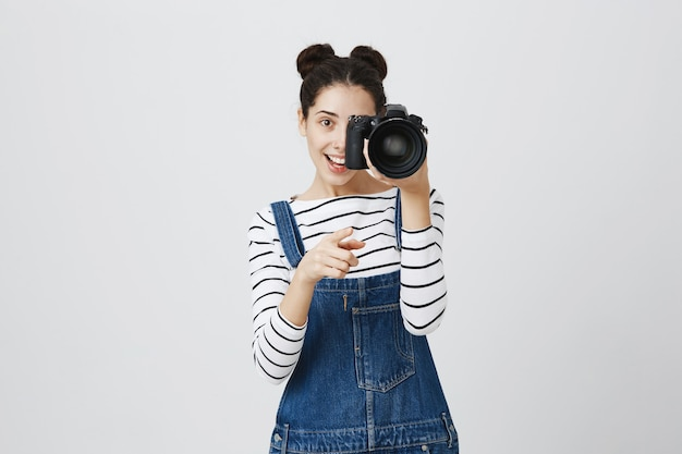 Веселая девушка-фотограф, указывая на камеру и снимая на камеру