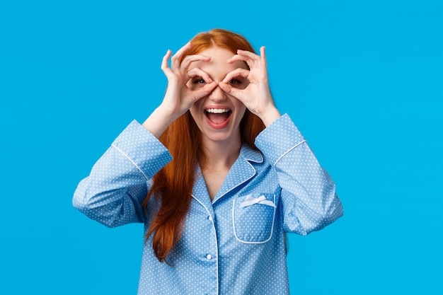 Amused girl seeing wonderful promo, want try out. attractive redhead woman in lovely pyjama make glasses with fingers, looking through smiling thrilled and excited, standing in nightwear