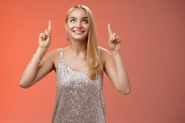 Amused gorgeous tender elegant european woman blond long hairstyle in silver glittering evening dress look pointing up curious gaze excitement see desired thing, standing red background joyful.