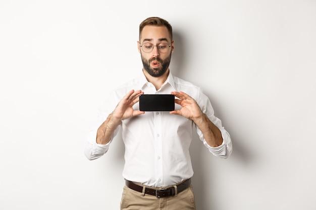 Забавный красивый парень показывает экран мобильного телефона, взволнованно глядя на онлайн-сайт, стоя