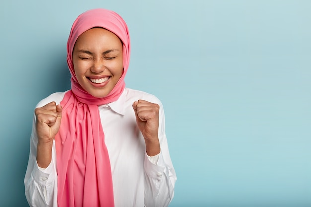 Amused happy arabian woman raises clenched fists, gains goal successfully, keeps eyes shut