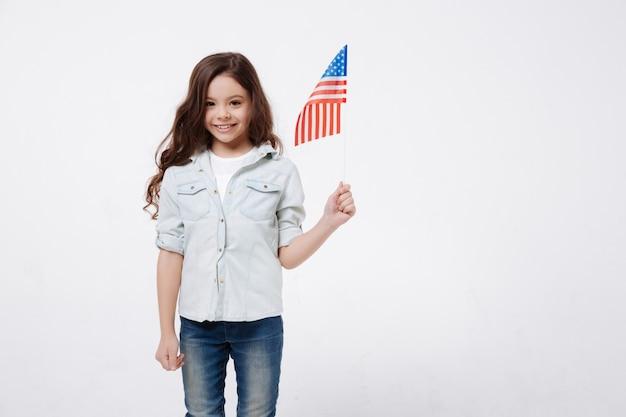 Веселая счастливая веселая девушка держит американский флаг, улыбаясь и стоя у белой стены