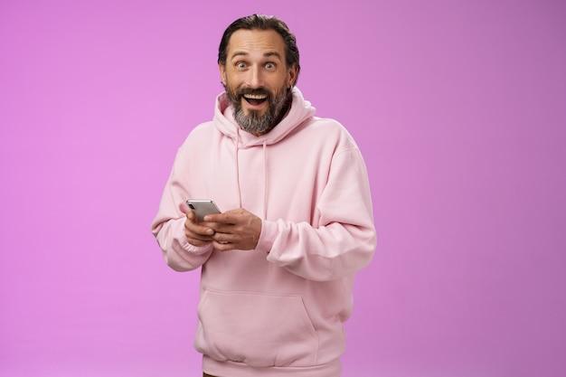 Забавный счастливый очарованный взрослый зрелый кавказский бородатый мужчина в розовой толстовке с капюшоном, задыхаясь, впечатлен, держа в руках смартфон, смотрю в камеру, удивлен покупкой классного нового телефона, поражен тем, насколько удобно.