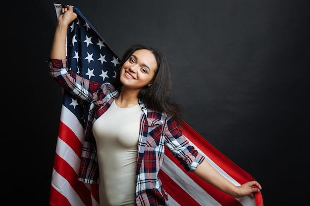 Веселая счастливая женщина забавляется и улыбается, держа американский символ и стоя изолированной у черной стены