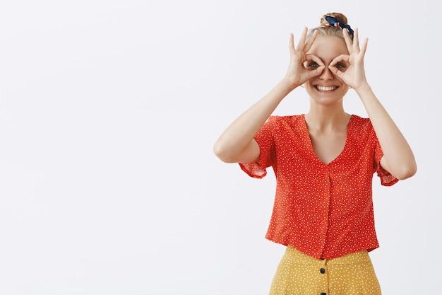 Giovane ragazza bionda divertita e felice che posa contro il muro bianco
