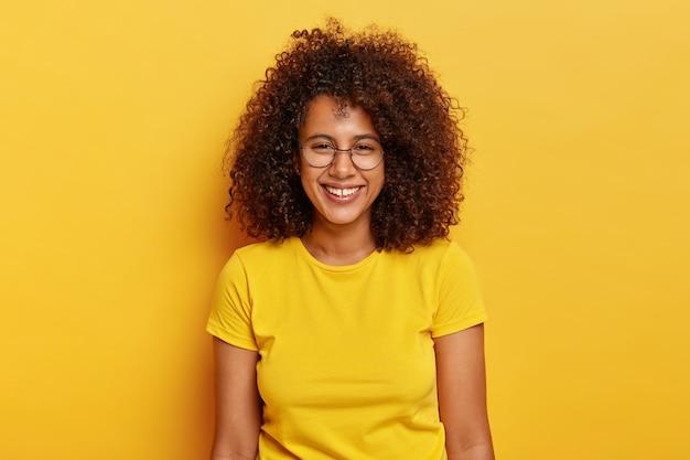 Веселая радостная афроамериканка смеется во время увлекательной беседы, широко улыбается, показывает белые зубы, носит прозрачные очки и желтую футболку, зубасто улыбается, поощряет выражение