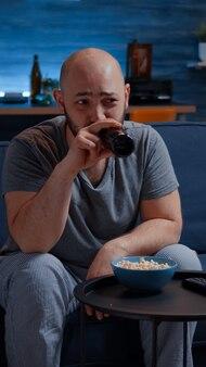 Забавный мужчина смеется, смотря комедию по телевизору и ест попкорн