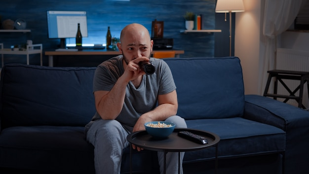 Amused man laughing watching comedy movie on tv eating popcorn