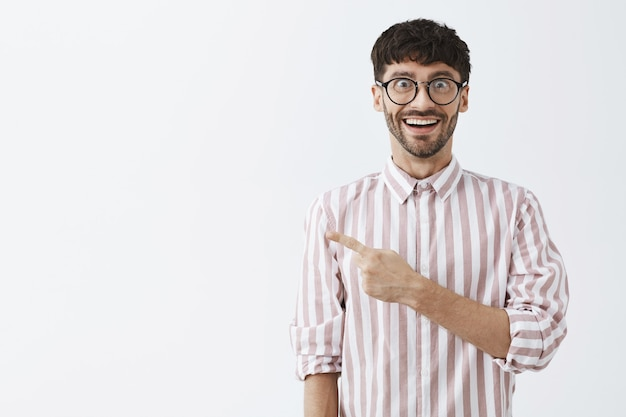 Amused stylish bearded guy posing against the white wall with glasses