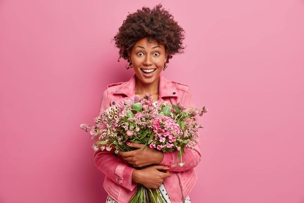 面白がって驚いた暗い肌の女性は、かわいい花の花束を抱き、記念日で友人を祝福し、ピンクのファッショナブルなジャケットを着て、屋内に立っています。お祝い、特別な日