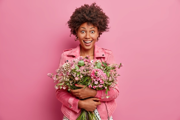 Amused surprised dark skinned woman embraces bouquet of pretty flowers, going to congratulate friend with anniversary, wears pink fashionable jacket, stands indoor. celebration, special occasion