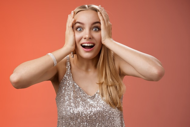 Amused surprised excited young blond attractive woman in silver glittering stylish dress hold head hands widen eyes speechless look camera unbelievable thrill fan see famous person, red background.