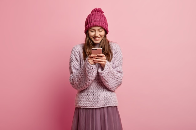 Amused upbeat pleased young woman holds smartphone, wears winter hat and knitted jumper