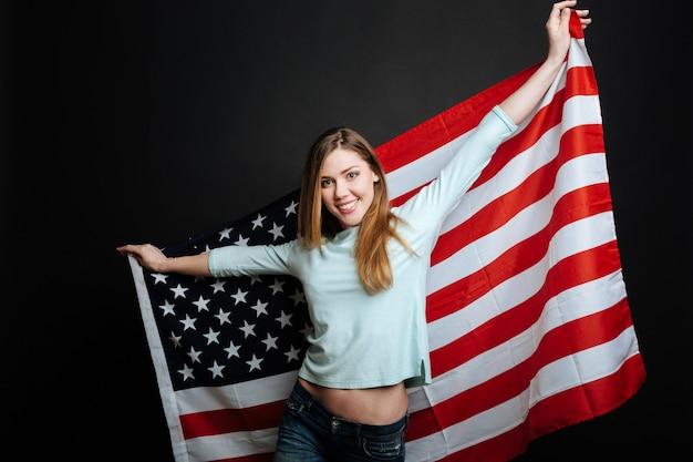 Веселая молодая веселая женщина улыбается и выражает радость, держа флаг сша и стоя изолированной в черной стене