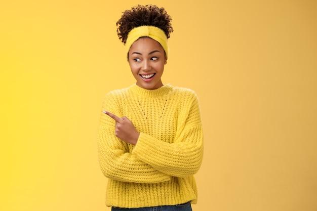 재미있는 젊은 밀레니엄 아프리카 여성이 우스꽝스럽게 왼쪽을 가리키며 활짝 웃고 있는 흥미로운 흥미로운 장소를 보여주고 우리 친구들은 광고, 노란색 배경을 나타내는 제품을 홍보합니다.