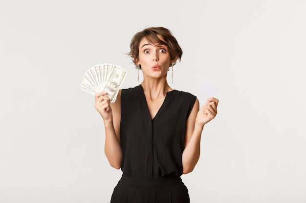 Забавная молодая девушка с кредитной картой и деньгами, глядя на что-то удивительное, стоящее белое.