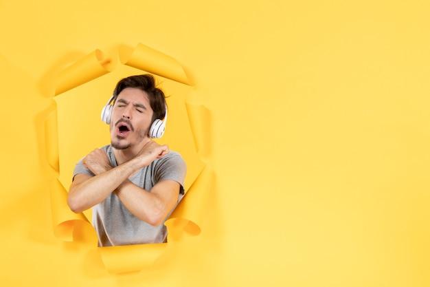 찢어진 노란 종이 배경 초음파 오디오 사운드에 헤드폰을 끼고 즐거운 젊은 남성