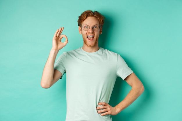 赤い髪の若い男を面白がって、眼鏡とtシャツを着て、大丈夫なサインを見せて、興奮して笑って、何かをチェックしてそれを承認し、ターコイズブルーの背景の上に立っています。