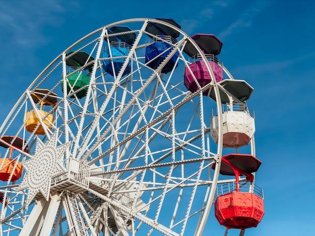 Парк аттракционов, красочное колесо обозрения. вид сбоку.