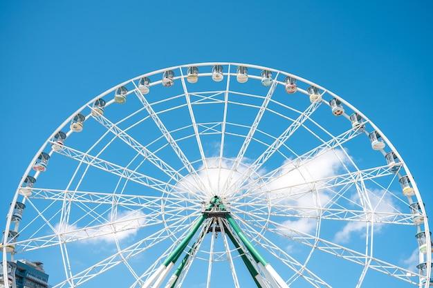 Amusement park and ferris wheel against the blue sky