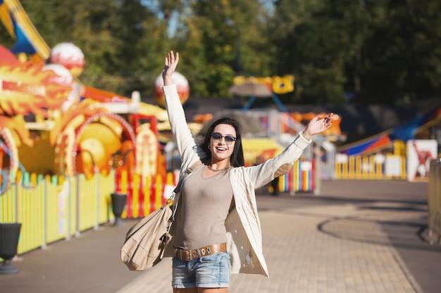 Парк аттракционов. молодая женщина счастлива и прыгает.