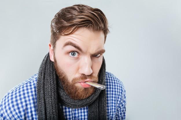 Забавный бородатый молодой человек в шарфе с термометром во рту над белой стеной