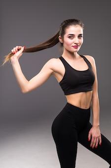 Забавная веселая фитнес девушка держит ее длинные волосы в хвост над белой стеной
