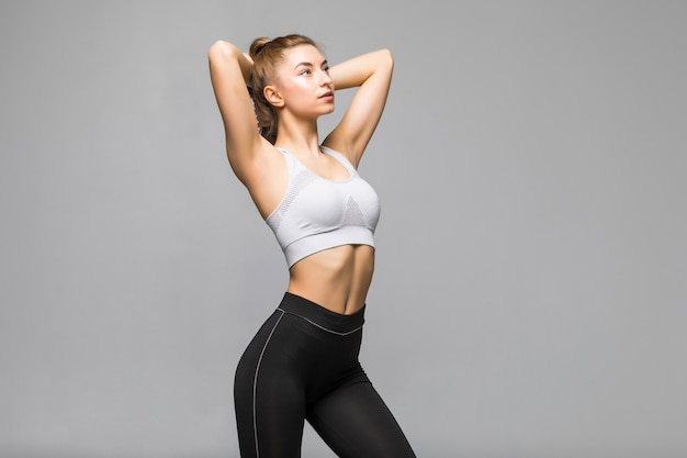Amusing cheerful fitness girl in pink top holding her long hair in ponytail