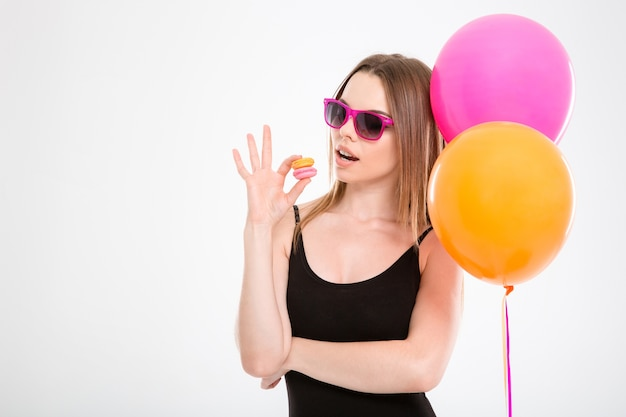 Amusing concentrated beautiful young woman in pink sunglasses with colorful balloons eating macaroons