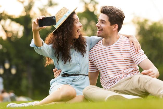 Забавная пара сидит на зеленой траве в парке и делает селфи на мобильном телефоне