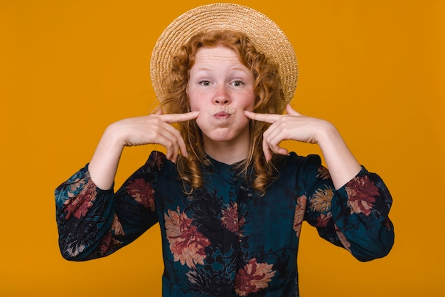 Amusing curly female with ginger hair fooling around in studio with colored background
