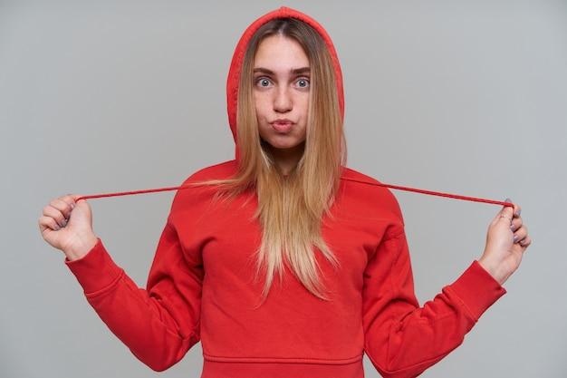 Divertente e carina giovane donna bionda in felpa con cappuccio rossa che fa una faccia buffa e divertirsi sul muro grigio