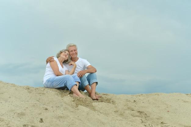 Забавная пожилая пара пошла на пляж, чтобы насладиться морским бризом