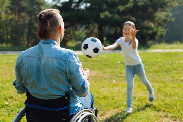 面白いゲーム。小さな女の子が投げたボールをキャッチし、公園で週末を楽しんでいる車椅子の若い男の背面図